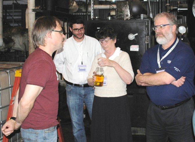 In March a contingent from Madison County traveled to Niagara Falls to tour JBI Inc. CEO John Bordynuik explains how the AG and rigid plastic is changed back into diesel fuel. Madison County Recycling Coordinator Sharon Driscoll holds a jar of diesel fuel, derived from discarded plastic. IDA Director Kipp Hicks, second from left, and Kevin Voorhees of Barton and Loguidice Engineers, right, pay close attention to Bordynuik's description.