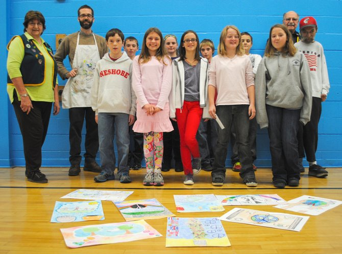 Students of the Neshobe Elementary School, participating in the Brandon-Forestdale Lions Club Peace Poster Contest, stand behind their work in the school cafeteria. The Lions Club announced three winners with the first place winner moving on to the statewide contest.