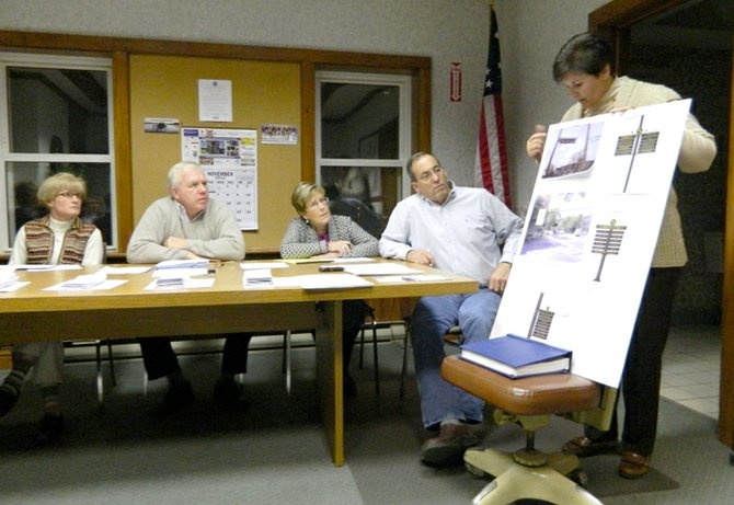 Sue Dove, executive director of the Skaneateles Area Chamber of Commerce, right, shows the village board printed examples of the new signs the chamber would like erected in the village to direct visitors to businesses that reside off Genesee Street. From left, Trustee Sue Jones, Mayor Marty Hubbard, Village Clerk Patty Couch and Trustee Marc Angelillo.