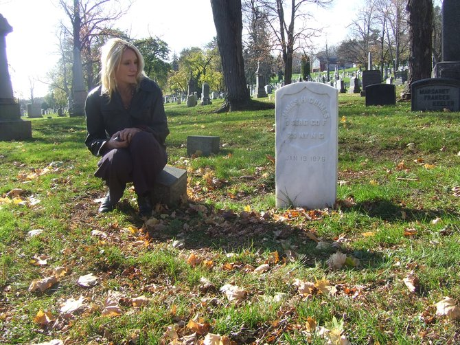 Historian KellyAnn Grimaldi looks at one of the restored Civil War gravestones at St. Agnes Cemetery.