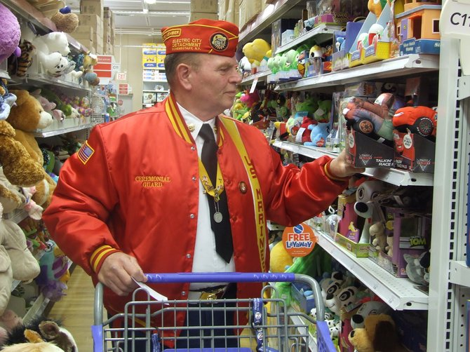 "A Marine Corps League volunteer picks a toy to add to the Toys for Tots Train at Toys ""R"" Us."