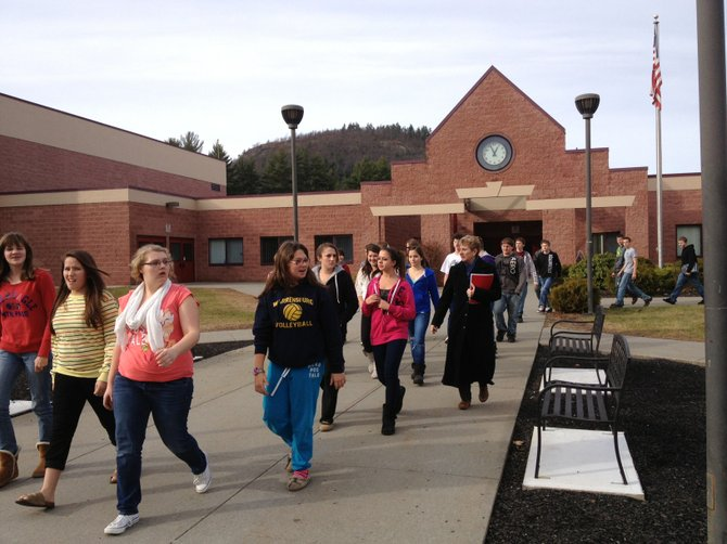 Students evacuate Warrensburg High School and walk toward shelter in the school bus garage Tuesday afternoon after a bomb threat was found scrawled on a bathroom wall.