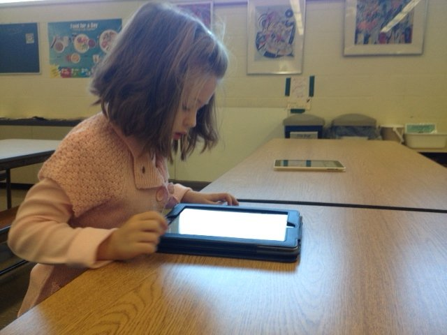 Emily Gokey, a first-grader at Elsmere Elementary, votes on an iPad during Bethlehem Central School Districts mock presidential election vote.  