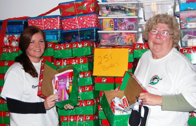 Ellecia Schaefer and Jeanie Graver present 141 boxes ready to be shipped to children worldwide through Operation Christmas Child at the Westport Bible Church.