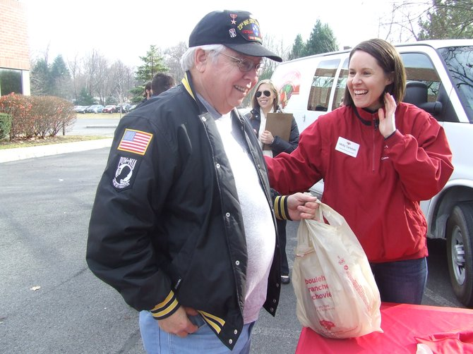 Molly Tarleton of Hannaford Supermarkets hands a veteran a free turkey.