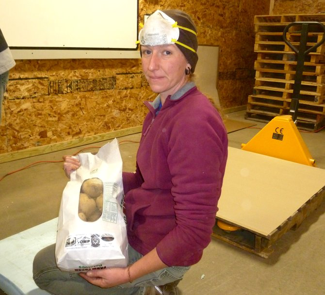 Salvation Farms' founding Director, Theresa Snow, holds the first bag of inmate packed potatoes – a significant milestone for her organization.