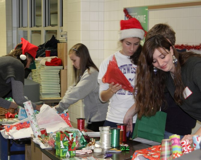 Cazenovia High School students Mimi Gabor, center, Jessy Silfer and Samantha Fox wrap presents for the 2011 Toy Shop. This year, the fifth annual event will be held on Dec. 7 and 8 at Burton Street Elementary School.