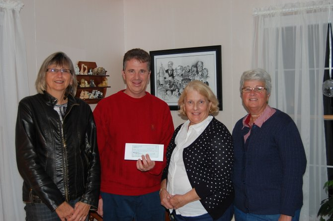 Grand Knight Brian Dristle (center) presents a check to Skaneateles Ecumenical Food Pantry Board members (from left) Karen Haggerty, Judy Gelson and Sue Eckhardt.