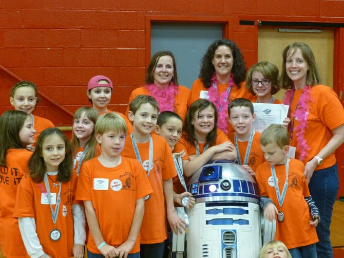 Members and coaches of the winning Minoa Mindstormers Robotics team show off the medals they won after qualifying for the Regional Championships of the FIRST LEGO League.