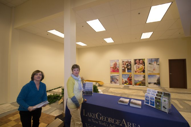 Warren County Tourism Department employees (left to right): Sue Tucker and Tanya Brand take a break while setting up brochures and leaflets at the county's new Information Center in the Adirondack Factory Outlet Mall on Rte. 9 just north of I-87 Northway Exit 20. 