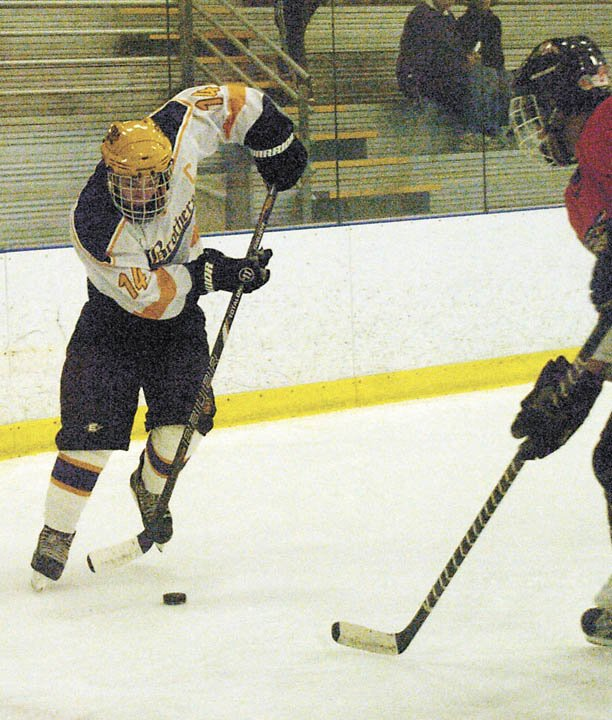 Christian Brothers Academy's John Basset tries to pass the puck past Mamaroneck's Trey Herlitz-Ferguson during Saturday's championship game of the Shaker/Colonie Thanksgiving Tournament.