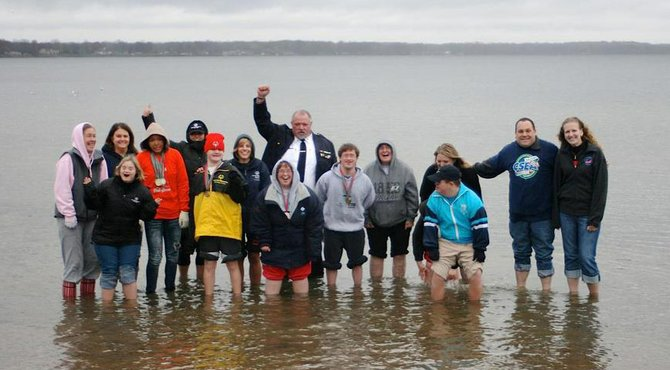 Cazenovia residents Diane Budnar, left center, and Ryan Goldacker, right center, stand with a group of Special Olympics New York athletes and local residents in the shallow waters of Oneida Lake. The group, along with area law enforcement officials, will completely submerge themselves in the frigid waters at noon on Dec. 2 as part of the Sixth Annual Central New York Polar Plunge. Funds raised leading up to and during the event benefit Special Olympics.