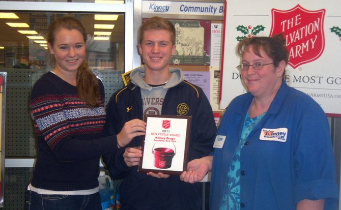 Kinney Drugs store supervisor Jen Winn, right, displays the 2011 Red Kettle Award the store earned from the Salvation Army. With Winn are Kaitlyn Gerber, left, and Brody Kellish who both served as Cazenovia High School student coordinators for the event.