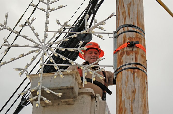 Matt Thomas, a worker at Frontier Communications, puts up a snowflake light on the utility pole next to the Johnsburg Town Hall in North Creek Thursday, Nov. 29. In all, he put up 15 snowflake decorations around town for the holiday season. This is the fourth year he has volunteered for this project, which is completed on his own time, and Frontier loaned the bucket truck.