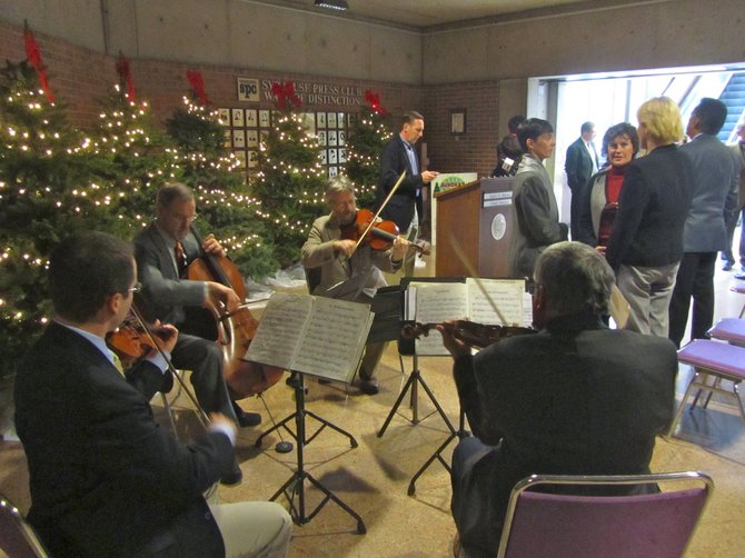 A string quartet composed of musicians from Syracuse's newly branded symphony performs in the Civic Center lobby following a press conference Nov. 18. County Executive Joanie Mahoney and Syracuse Mayor Stephanie Miner can be seen talking with college music professor Heather Bookman.