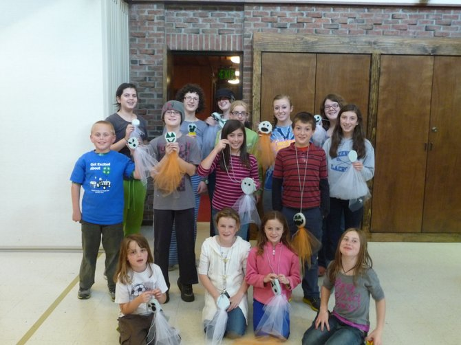 "Members of the local 4-H group, the Lincklaen Shamrocks, gather for a group photo and display the ghost and pumpkin hanging decorations they made with Styrofoam and a light transparent fabric called ""tulle."""