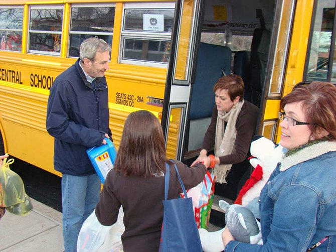 Staff from Scotia-Glenville Schools fill a bus with donated gifts and wrapping supplies for Schenectady's City Mission.