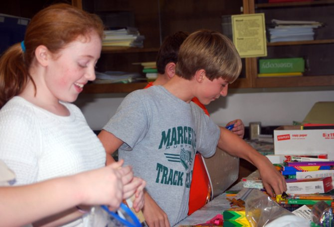 C.S. Driver Middle School students Maggie Brennan (left) and Caleb Wetherell assemble supply kits for victims of Hurricane Sandy in Rockaway Beach, Queens.