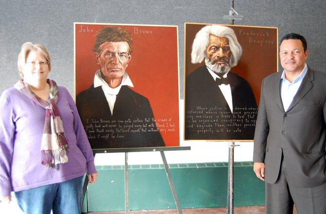 Alice Keesey Mecoy and Kenneth B Morris Jr. stand next to Robert Shetterly's portraits of their great-great-great grandfathers; Frederick Douglass and John Brown.