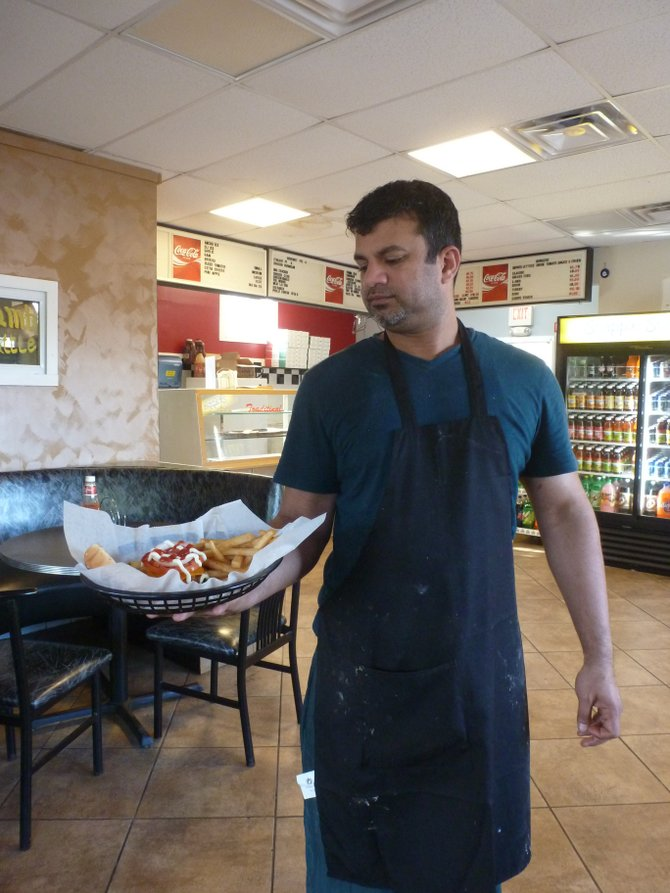 Dave Khan, owner of Dave&#39;s Burgers in Colonie, with one of his signature Kobe burgers. 