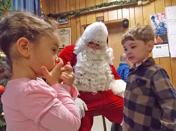 Three-year-olds Tianna and Logan, both of Minerva, say hello to Santa Claus Saturday, Dec. 1 at the Breakfast with Santa event at the North Creek Volunteer Fire Company. Below, the Johnsburg Central School Drum Corps leads the Dec. 1 parade.