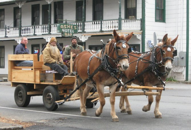 Guiding his Belgian mules down Hudson St. past the historic Ashe's Hotel, Todd Olden (front,right) gives passengers a ride during this weekend's Christmas in Warrensburgh festival.