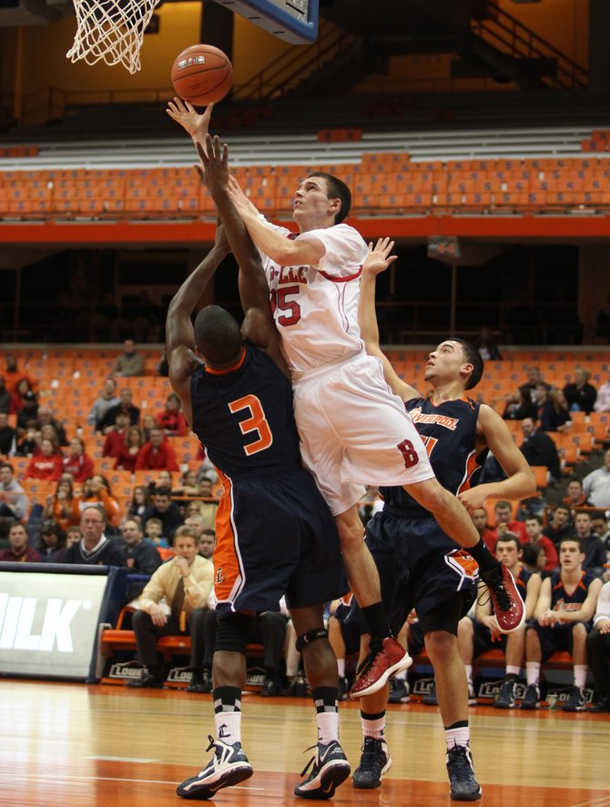 Baldwinsville sophomore guard Tim Marshall (15) goes over Liverpool's Caleb Taylor (3) and takes a shot during Sunday night's Tip-Off Classic at the Carrier Dome.