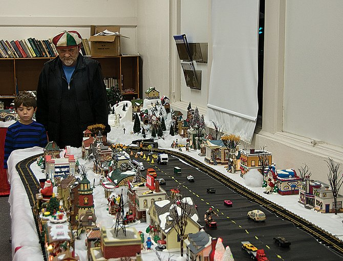 Matthew Macejka, 70, shows his grandson, Roman, the miniature Christmas Village he set up with family and friends at the Rotterdam Senior Center.