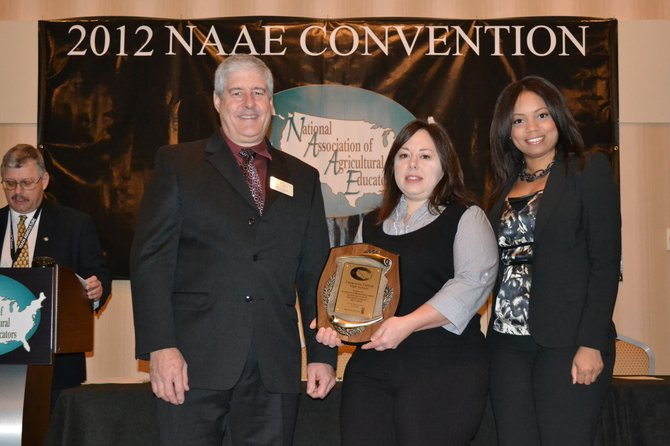 Ken Couture, 2011-12 NAAE President, left, presents Mandi Millen with a National Association of Agricultural Educators Outstanding Middle/Secondary Agricultural Education Program Award, as Monsanto Senior Education Manager Serena Gregory looks on during the Nov. 28 ceremony.