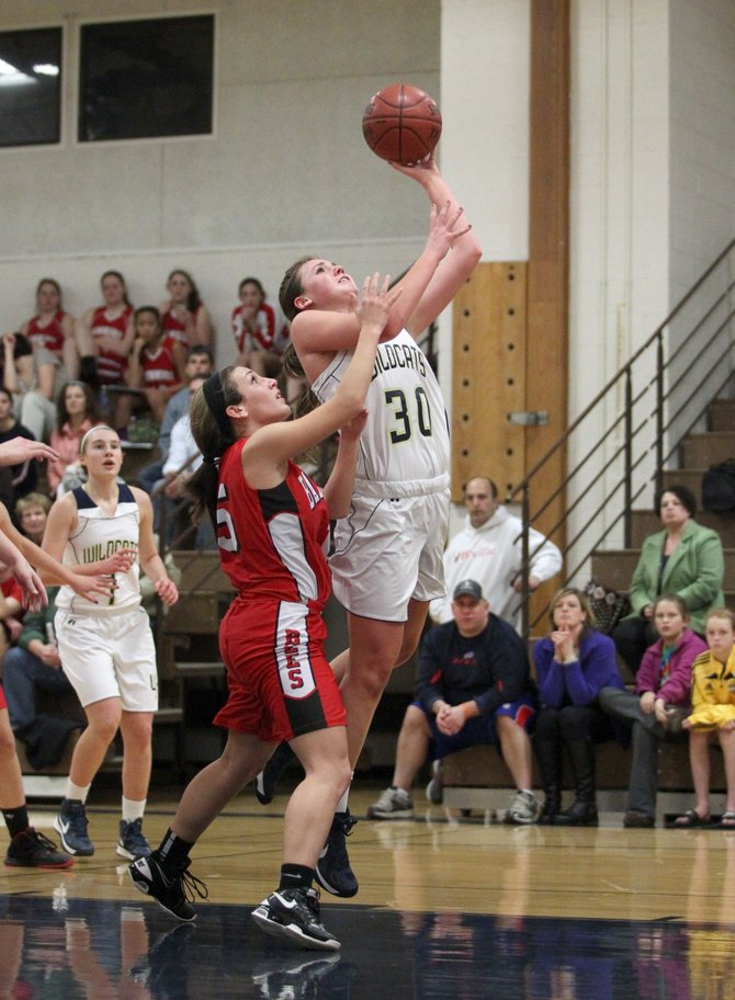 West Genesee sophomore forward Grace Osterdale (30) goes past Baldwinsville's Maggie D'Eredita (15) and rises to take a shot in Tuesday night's game against West Genesee. Osterdale and the Wildcats defeated the Bees 78-43 in an impressive season-opening effort.