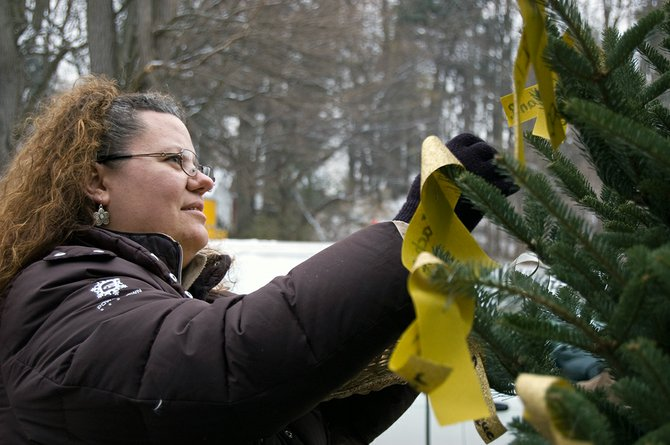 Jennifer Rathbone places a gold ribbon on the Childhood Cancer Awareness Christmas Tree her family setup in front of their Schenectady home. The tree is in honor of her daughter, Ila Jean, who died last year.