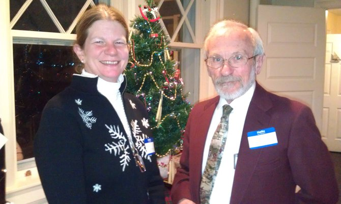 Horse expert Barb Linberg, left, stands beside  Dr. Fritz Koennecke  for a photo during the Limestone Creek Hunt Club annual holiday party.