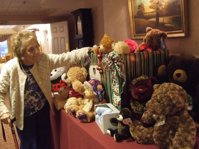 Esther Jasinski, 91, puts a teddy bear in the donations box for the teddy bear donation drive at the Loudonville Home for Adults.