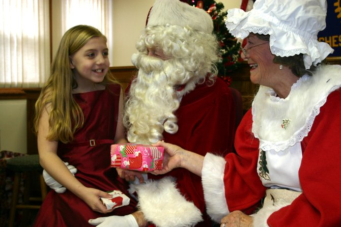 GIFT EXCHANGE — After asking for a drum for Christmas, Arianna Howe, 9, presents Santa and Mrs. Claus with gifts — a tie for the big elf and a snowman for his wife — while Santa's better half hands a present to the generous girl. About 300 children attended Santa's visit Saturday in Chestertown. The holiday event has been sponsored for 40 years by the Chestertown Rotary Club.