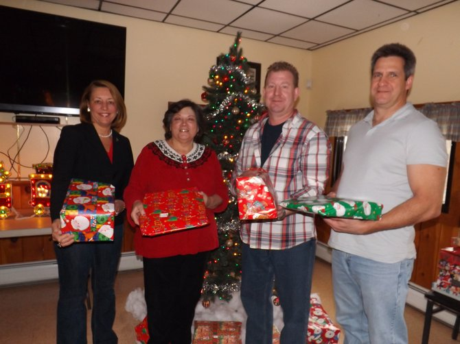 Joanne Yepsen, Mary Hagadorn, Paul Staulters and Michael O'Reilly hold presents for area children.