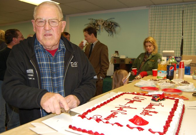 Rob Jerdo cuts into the cake during a celebration honoring his service as a member of the Wadhams Volunteer Fire Company for 68 years. Jerdo was one of the founding members of the company and put in many hours working on the firehouse, training firefighters and leading the unit.