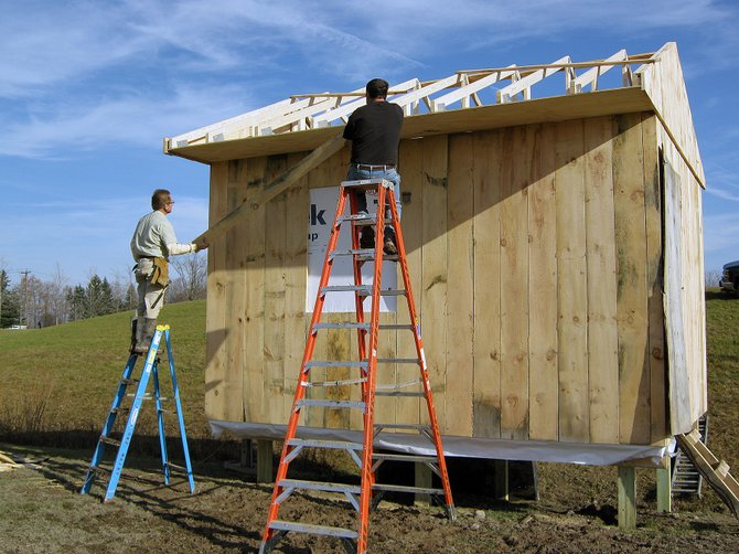 Cazenovia Central School District maintenance department employees Bill Poglitsh, left, and Sam Walrod work on the new scoring shed at the Sean Googin Sports Complex. The structure is made from wood that used to be a 70-foot tree on the front lawn of Cazenovia High School.