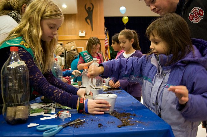 Eight-year-old Jackie Jasiewicz, front right, spoons some dirt out of a cup while making her own greenhouse with help from local Girl Scouts.