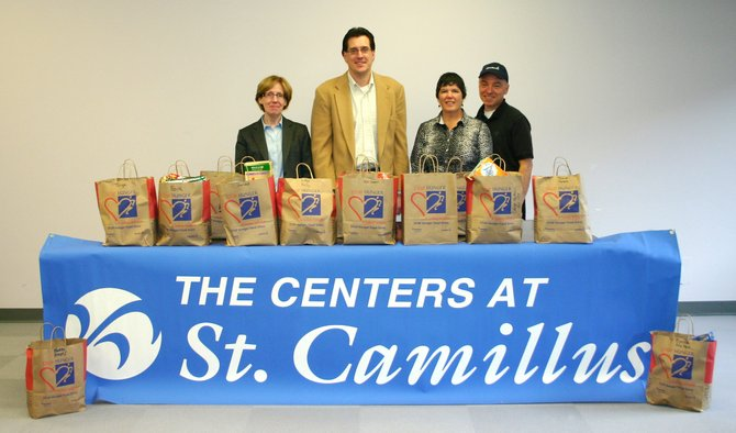 "Members of The Centers at St. Camillus community proudly display the results of their ""Stop Hunger"" food drive campaign. Pictured from left to right are: Aileen Balitz, president of The Centers at St. Camillus; Michael Schafer, vice president for the Nursing Facility; Mary Monteleone, general manager of Dining and Nutrition; and Rob Mackay, executive chef."