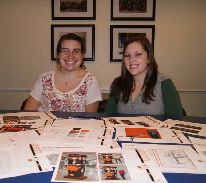 Cazenovia College Interior Design Program students Courtney Wallach, left, and Amanda Jones with materials from their kiosk presentation.
