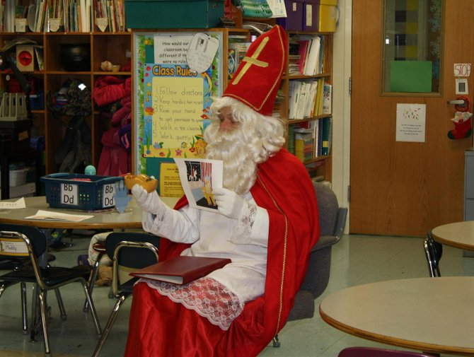 Sinterklaas, as portrayed by area resident Joost Brasz, a native of Holland, exhibits a traditional shoe Dutch children would place in front of their fireplaces in hopes of receiving treats for being well-behaved. Brasz, and his wife Ulla, originally from Sweden, visited the young students on Dec. 7 in their classrooms at Burton Street Elementary School.