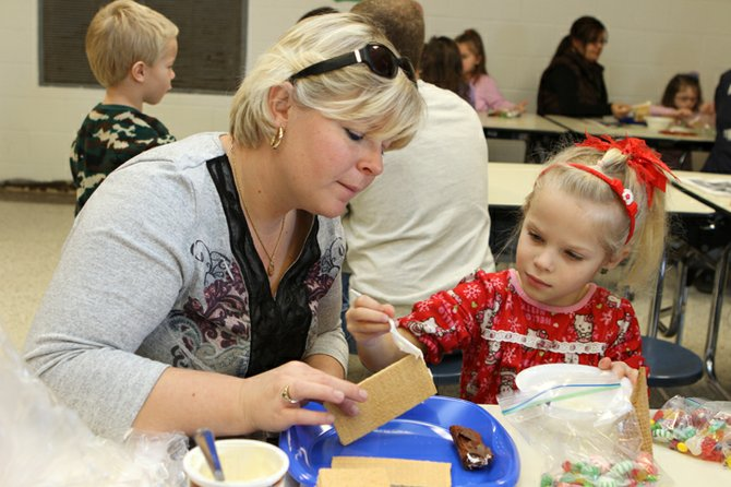 Erica Riemersma helps her daughter, Juliana, make a gingerbread train during Polar Express Day at Moriah Central School.