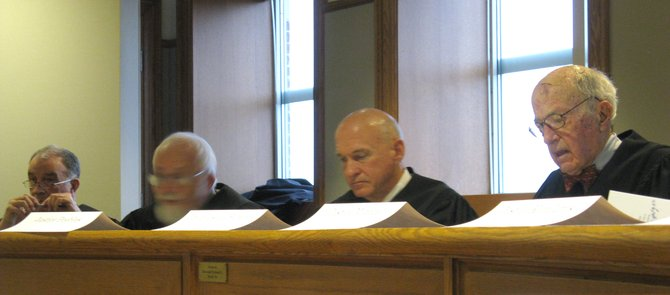 "Cazenovia resident Judge Stewart F. Hancock Jr., right, reads from the docket during a mock-Supreme Court trial study on Dec. 10 at Syracuse University Law School. Beside Hancock, who acted as presiding justice, are fellow members of the ""Room 400 Supreme Court""; Judge David Peebles, Professor Travis Lewin and Emil Rossi."