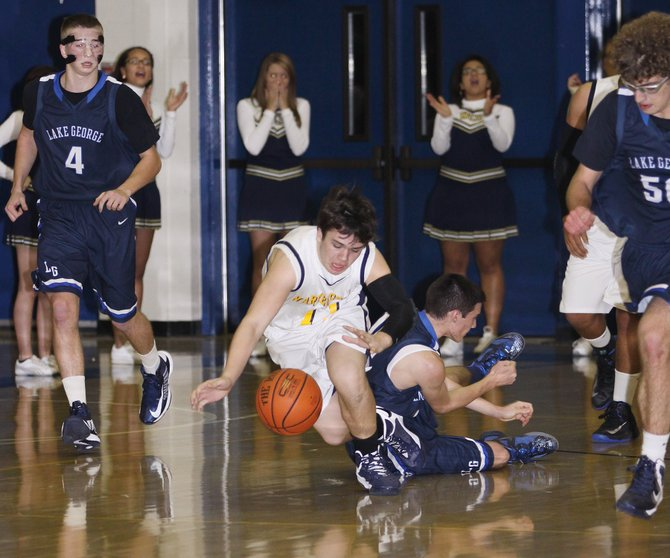 Warrensburg&#39;s Jake Nemec (center left) plows past Lake George&#39;s Andrew Zibro while Joel Wincowski (left); and Jeff Nataly (right) jog downcourt in a game held between the two rival teams Tuesday Dec. 18. Lake George won the physical game by a score of 68 to 28.