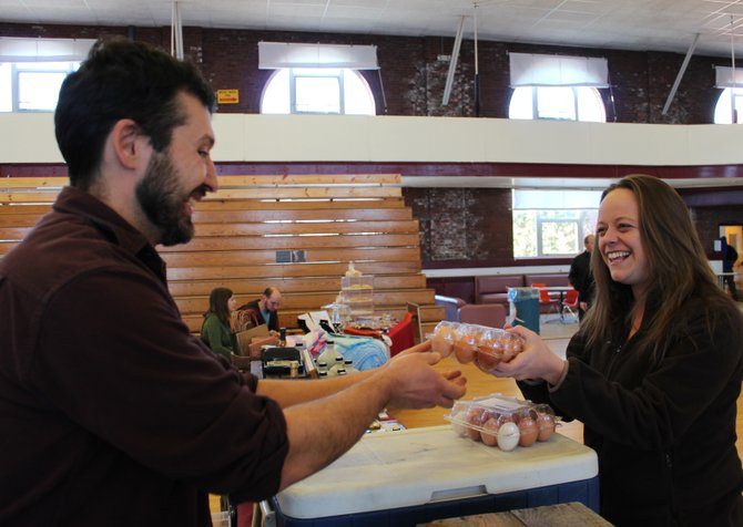 Emily Blauvelt buys eggs from Josh Vaillancourt of Woven Meadows Farm in Saranac. The farm opened in March and offers CSA memberships.