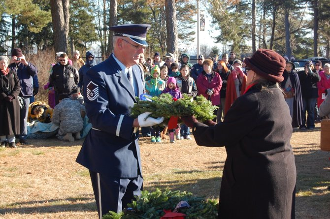 Military personnel receive wreaths to place on soldiers graves at the Old Post Cemetery during the annual Wreaths Across America.