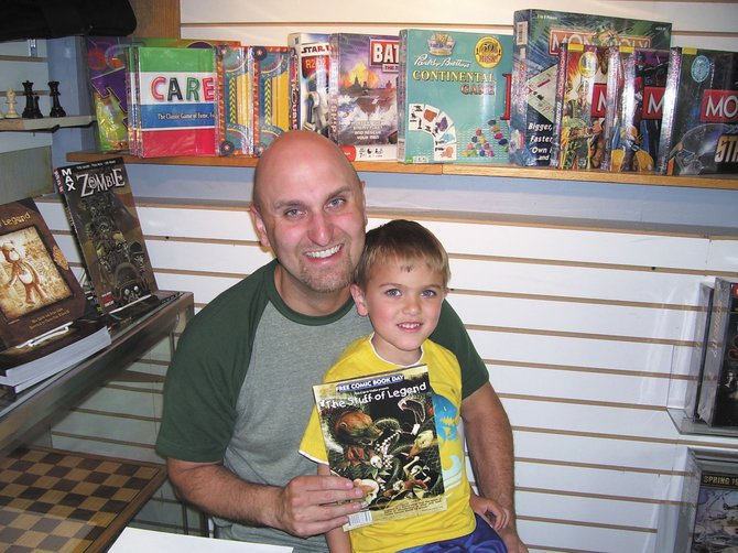 Le Moyne College English Professor Mike Raicht is the author of the successful series The Stuff of Legend, which made the New York Times bestseller list in 2010. Raicht is pictured above at a book signing event with his son, Austin, a few years back.