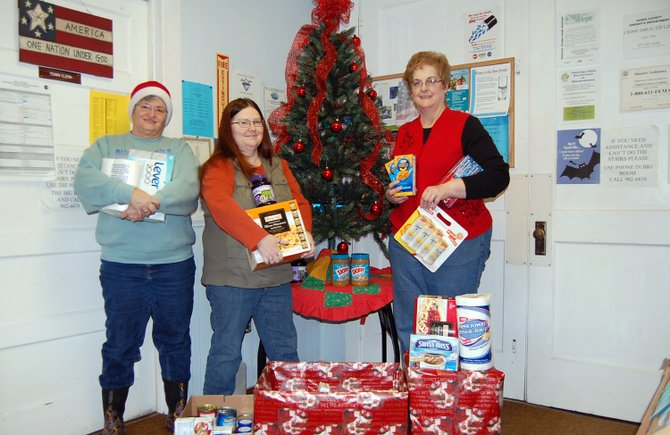 Dawn St. Louis, Robin Crandall and Shelia Borden stand near the presents at the Westport Town Offices.