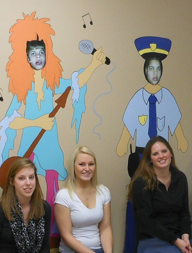 Caz College students Katie Hughes, left, Ashley Dyer and Megan Sitarek pose in front of the characters they painted at Casey's Place, a respite center in Syracuse.