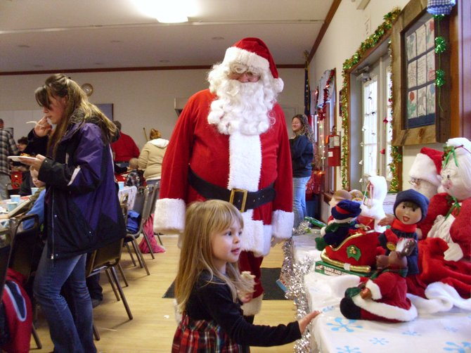 CHRISTMAS WONDER — Santa pauses in his duties at the Thurman Christmas Party Saturday Dec. 15 to observe a child entranced by handmade dolls on display at the event. See inside for details about the party, which shattered previous attendance records.